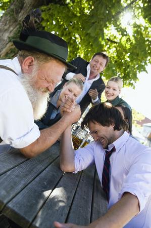 Germany,Bavaria,Upper Bavaria,Two Men In Beer Garden Arm Wrestling