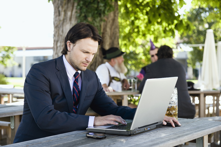 Germany,Bavaria,Upper Bavaria,Young Business Man In Beer Garden Using Laptop