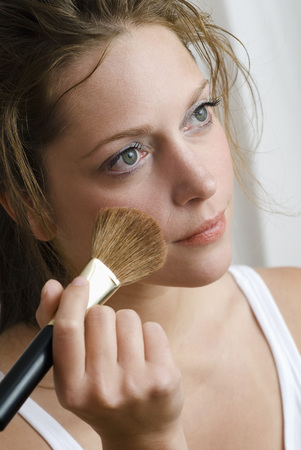 Young Woman Using Make-Up Brush, Close Up LANG_EVOIMAGES