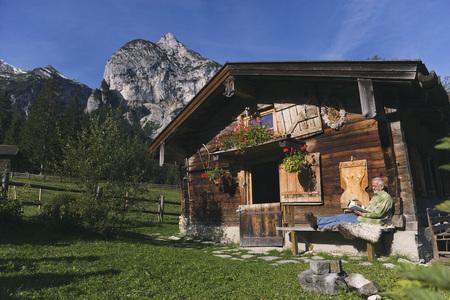 Austria,Karwendel,Senior Man Sitting In Front Of Log Cabin,Reading A Book LANG_EVOIMAGES