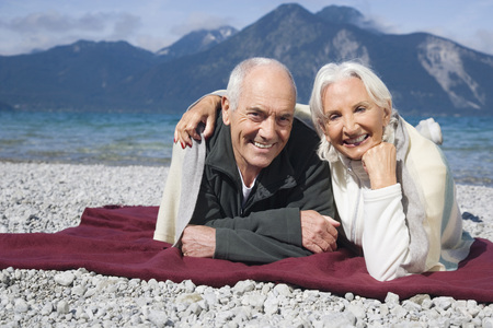 Germany,Bavaria,Walchensee,Senior Couple Relaxing On Lakeshore
