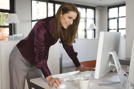 Young Woman In Office Using Laptop