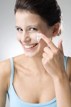 cremas faciales: Mujer joven que aplica la crema de belleza, cierre para arriba