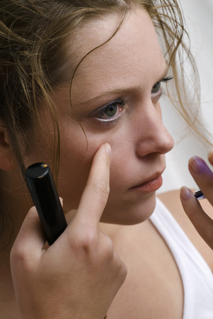 Young Woman Checking Face In Hand Mirror, Close Up