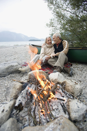 Germany,Bavaria,Walchensee,Senior Couple Sitting At Campfire LANG_EVOIMAGES