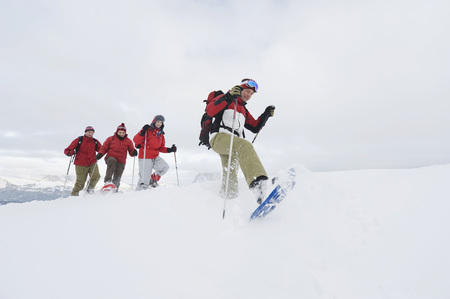 Italy, South Tyrol, Four People In A Row, Snowshoeing LANG_EVOIMAGES