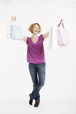 Young Woman Holding Shopping Bags, Smiling, Portrait LANG_EVOIMAGES