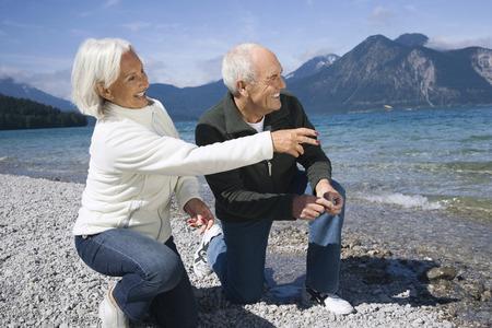 cowering: Germany,Bavaria,Walchensee,Senior Couple Looking Across Lake LANG_EVOIMAGES