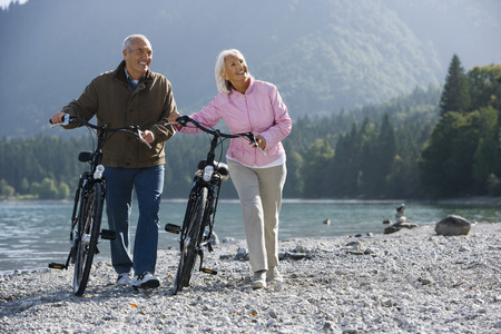 Germany,Bavaria,Walchensee,Senior Couple Pushing Bikes Across Lakeshore LANG_EVOIMAGES