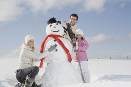 Germany, Bavaria, Munich, Family Making A Snowman, Portrait