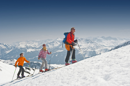 Austria, Salzburger Land, Altenmarkt, Zauchensee, Three Persons Cross Country Skiing In Mountains, Side View