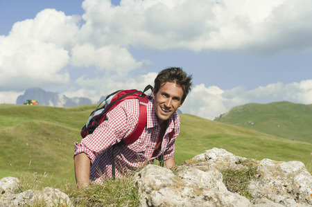 Italy,South Tyrol,Man Standing By Rock,Smiling,Portrait LANG_EVOIMAGES