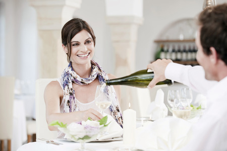 front facing: Couple In Restaurant,Man Pouring Wine Into Glass LANG_EVOIMAGES