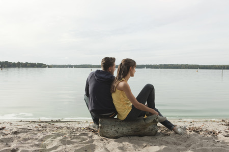 Germany,Berlin,Lake Wannsee,Young Couple Relaxing On Beach,Rear View