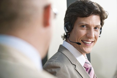 Germany, Munich, Man Wearing Headset, Businessman In Foreground