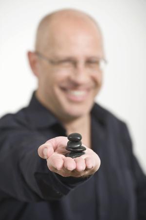 Businessman Holding Pile Of Pebbles, Smiling, Portrait