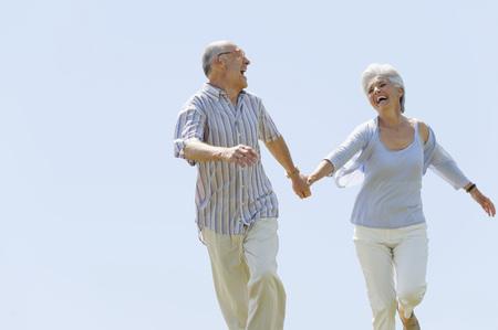 Senior Couple Running Hand In Hand,Portrait