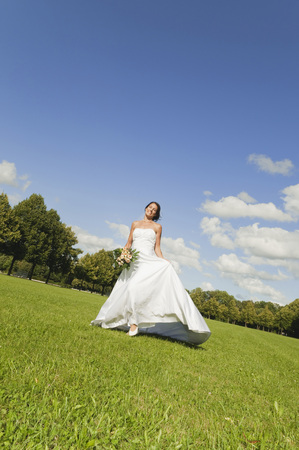 marrying: Germany,Bavaria,Bride Walking In Park,Holding Bunch Of Flowers,Smiling,Portrait LANG_EVOIMAGES