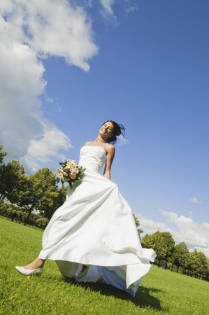 marrying: Germany,Bavaria,Bride Running In Park,Holding Bunch Of Flowers,Smiling,Low Angle View LANG_EVOIMAGES