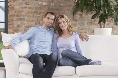 Germany,Cologne,Couple Sitting On Sofa,Smiling,Portrait LANG_EVOIMAGES