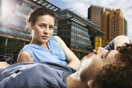 Germany,Berlin,Young Couple Lying In Meadow,High Rise Buildings In Background