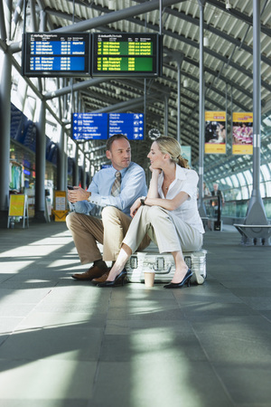 Germany, Leipzig-Halle, Airport Businessman And Businesswoman Sitting On Suitcase