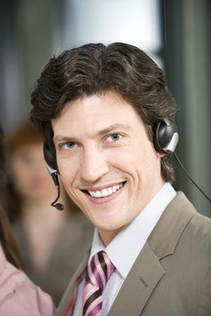 Germany, Munich, Man Wearing Headset, Smiling, Portrait LANG_EVOIMAGES