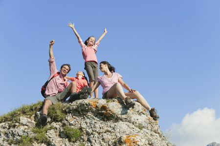 conquering adversity: Italy,South Tyrol,Family Sitting On Rock,Cheering,Portrait