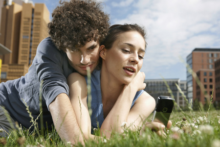 Germany,Berlin,Young Couple Lying In Meadow,Woman Holding Mobile Phone,Portrait,Close-Up