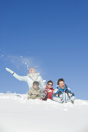 Italy, South Tyrol, Seiseralm, Family Sitting In Snow, Laughing LANG_EVOIMAGES