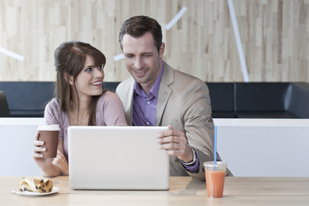 Germany, Cologne, Couple In Cafe Using Laptop
