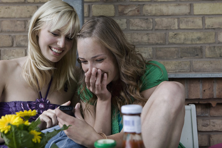 Germany,Berlin,Young Women Looking At Mobile Phone,Smiling