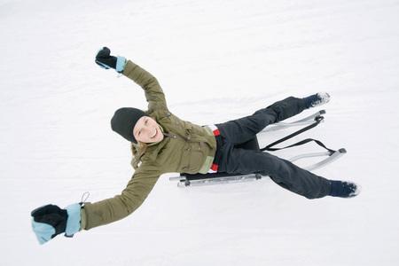 Italy, South Tyrol, Seiseralm, Girl (12-13) Sledding Downhill, Portrait LANG_EVOIMAGES