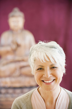 spiritual beings: Portrait Of A Senior Woman In Background A Buddha Statue
