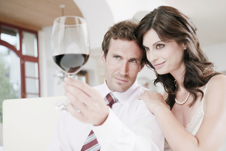 Couple In Restaurant,Man Holding Glass Of Red Wine,Portrait LANG_EVOIMAGES