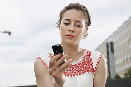 Germany,Berlin,Young Woman Holding Mobile Phone,Portrait,Close-Up
