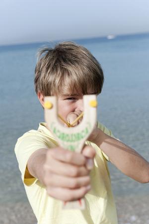 Spain,Mallorca,Boy (8-9) Using Sling-Shot LANG_EVOIMAGES