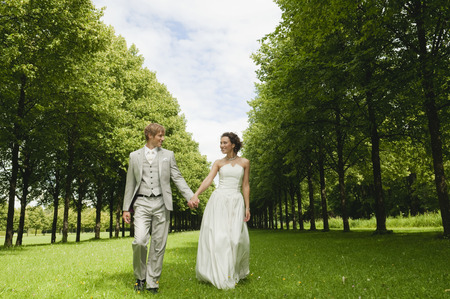 marrying: Germany,Bavaria,Bridal Couple In Park Walking Hand In Hand,Smiling,Portrait LANG_EVOIMAGES