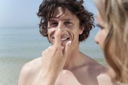 cremas faciales: España, Mallorca, mujer aplicando crema solar en la nariz del hombre