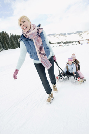 Italy, South Tyrol, Seiseralm, Woman Pulling Children (6-7) (8-9) On Sled