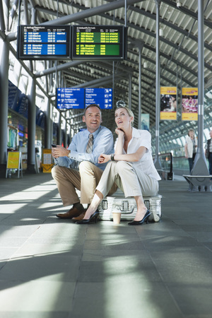 Germany, Leipzig-Halle, Airport, Businessman And Businesswoman Sitting On Suitcase
