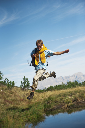Austria,Salzburger Land,Man Jumping By Waterside,Laughing,Portrait LANG_EVOIMAGES