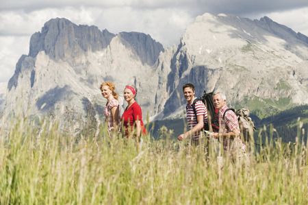 Italy,Seiseralm,Four Persons Hiking,Side View,Smiling,Portrait LANG_EVOIMAGES