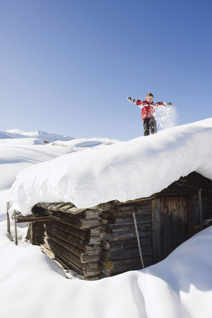 Italy, South Tyrol, Seiseralm, Boy (4-5) Standing On Snow-Covered Roof Of Log Cabin LANG_EVOIMAGES
