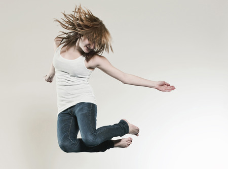 feet naked: Teenage Girl (16-17) Jumping Against Gray Background LANG_EVOIMAGES