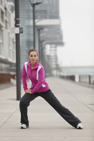 street shot: Germany,Cologne,Young Woman Doing Exercise,Portrait