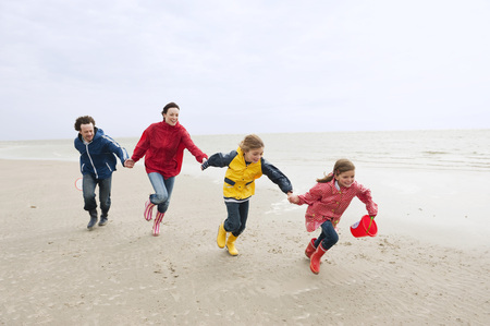 Germany,St Peter-Ording,North Sea,Family Holding Hands And Running On Beach