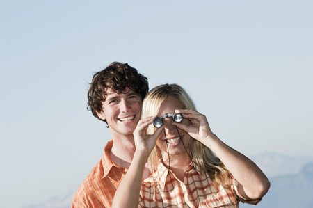 Young Couple Standing,Woman Uses Binoculars