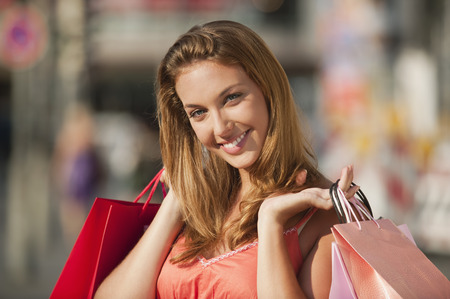 Germany,Munich,Karlsplatz,Young Woman With Shopping Bags,Smiling,Portrait LANG_EVOIMAGES