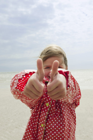 Germany,North Sea,Stpeter-Ording,Girl (6-7) In Rain Coat Showing Thumbs Up Sign On Beach